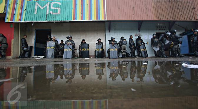 Polisi dengan menggunakan tameng bersiaga di kawasan Kalijodo, Jakarta, Senin (29/2). Ribuan personel dari Polda Metro Jaya, TNI, Satpol PP dikerahkan untuk mengamankan penggusuran kawasan Kalijodo. (Liputan6.com/Immanuel Antonius)