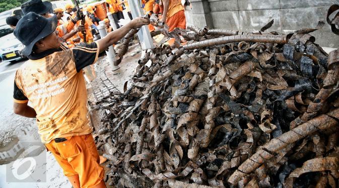 Petugas kebersihan mengumpulkan bungkusan kabel yang menyumbat saluran air di Jalan Merdeka Selatan, Jakarta, Senin (29/2). Basuki Tjahaja Purnama (Ahok) mengatakan adanya dugaan sabotase banjir akibat limbah kulit kabel itu. (Liputan6.com/Faizal Fanani)