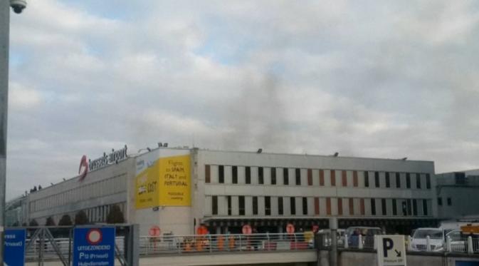 Asap hitam terlihat mengepul dari bandara Zaventem di Brussel, setelah terjadi ledakan, Belgia, Selasa (22/3). Sedikitnya 13 orang tewas akibat dua ledakan beruntun yang mengguncang ruang keberangkatan bandara tersebut. (REUTERS/Peter van Rossum)