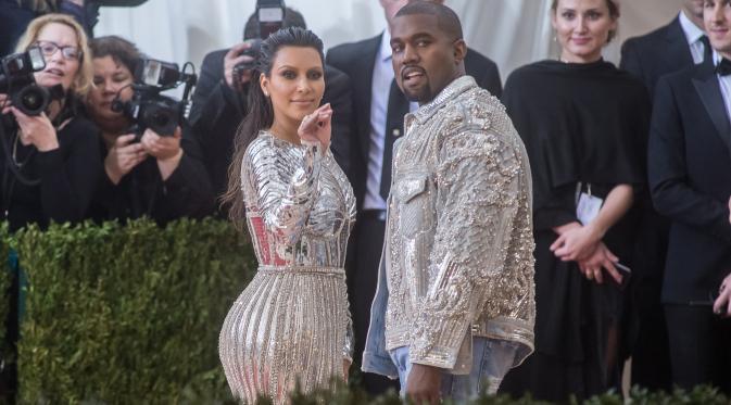 Pasangan Kanye West dan Kim Kardashian mencuri perhatian saat menghadiri ajang Met Gala 2016 di Metropolitan Museum of Art, New York City, Senin (2/5). Keduanya tampil senada mengenakan warna metalik perak. (Mark Sagliocco /Getty Images/AFP)