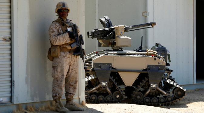 Tentara AS berdiri disamping Multi-Utilitas Tactical Transport (MUTT) saat latihan militer Rim Pasifik (RIMPAC) 2016 di Camp Pendleton, AS (13/7). Alat yang digunakan untuk patroli militer ini mempunyai teknologi canggih. (REUTERS / Mike Blake)