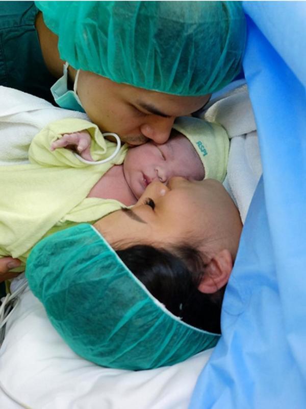 Sang suami Glenn mengunggah foto saat mencium buah hatinya setelah sekitar sejam istrinya melahirkan. Dalam foto, keduanya terlihat sedang mencium buah hatinya. (dok. Instagram/glennalinskie)