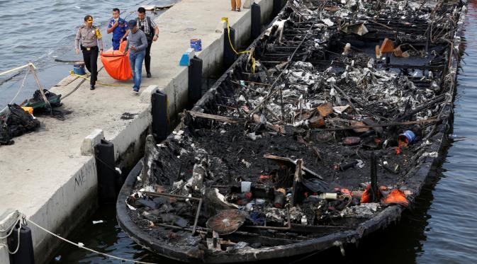 Petugas kepolisian bersama Tim SAR gabungan mengevakuasi kantong jenazah berisi penumpang kapal Zahro Express yang terbakar, di Pelabuhan Muara Angke, Minggu (1/1). Kapal penumpang tersebut terlihat dalam kondisi gosong. (REUTERS/Darren Whiteside)