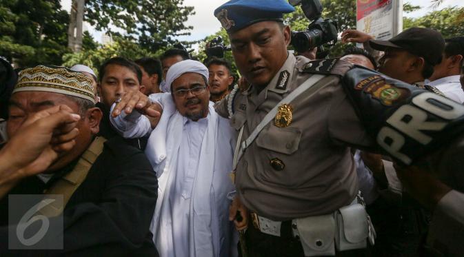 Imam Besar FPI, Habib Rizieq Shihab mendapat pengawalan setibanya di gedung Dit Reskrimsus Polda Metro Jaya, Jakarta, Senin (23/1). Habib Rizieq didampingi sejumlah rekannya dari FPI dan kuasa hukum untuk menjalani pemeriksaan (Liputan6.com/Faizal Fanani)