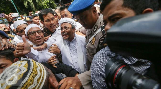 Imam Besar Front Pembela Islam (FPI), Habib Rizieq Shihab mengacungkan jempol setibanya di gedung Dit Reskrimsus Polda Metro Jaya, Jakarta, Senin (23/1). H (Liputan6.com/Faizal Fanani)