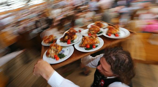 Seorang pelayan membawakan pesanan pengunjung saat Festival Bir Oktoberfest di Munich, Jerman, (19/9/2015). Oktoberfest di Jerman adalah festival bir terbesar di dunia yang akan berlangsung hingga 4 Oktober 2015. (AFP Photo / Josef Hildenbrand)